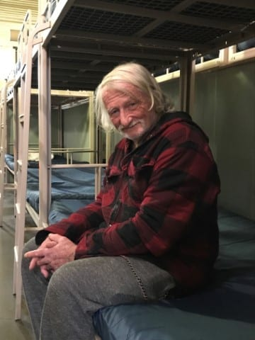 Photo of a client of Waterfront Rescue Mission sitting in an emergency homeless shelter, smiling