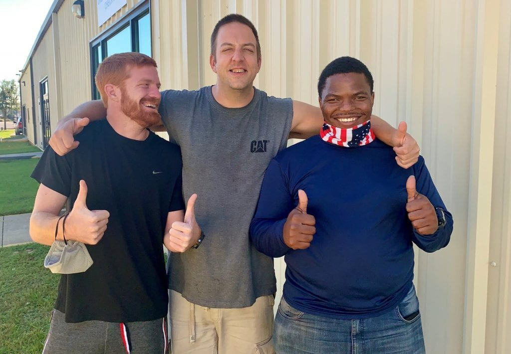 Photo of 3 clients of Waterfront Rescue Mission smiling and giving a thumbs up