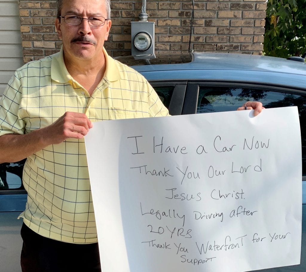 """Photo of a graduate of the Waterfront LifeBuilder Addiction Recovery Program holding up a sign that says """"I have a car now, thank you our Lord Jesus Christ. Legally driving after 20 years. Thank you Waterfront for your support."""""""