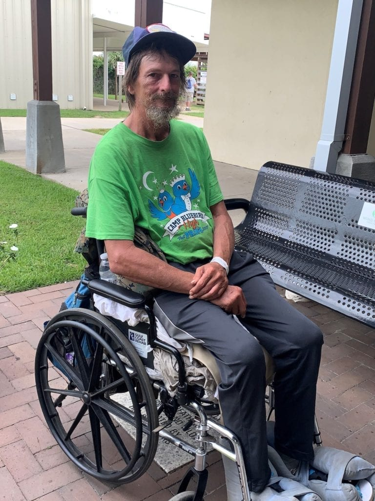 Photo of a client of Waterfront Rescue Mission in front of a Mission campus in a wheelchair