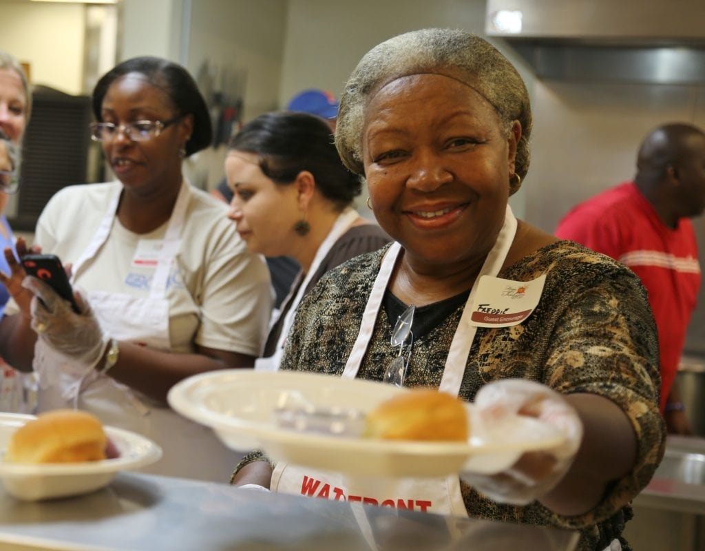 Photo of a woman serving food as a volunteer for Waterfront Rescue Mission