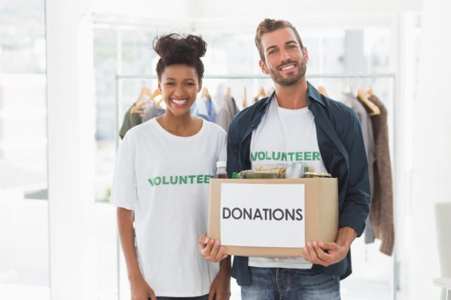 Photo of two volunteers smiling and holding a box of donations