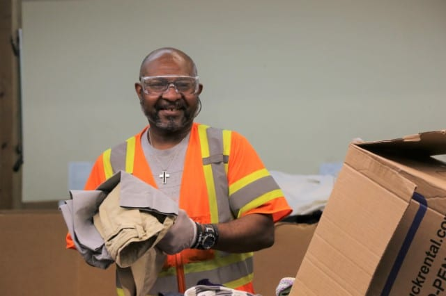 Photo of a client of Waterfront Rescue Mission working at a construction job and smiling