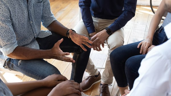 Photo of a group of people sitting in a circle and speaking to a counselor