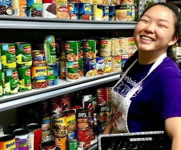 Photo of a young woman smiling and volunteering for Waterfront Rescue Mission