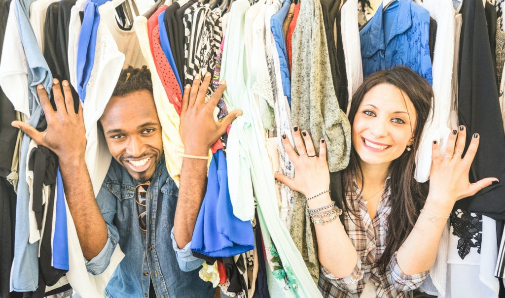 Photo of two customers smiling with hanging clothes